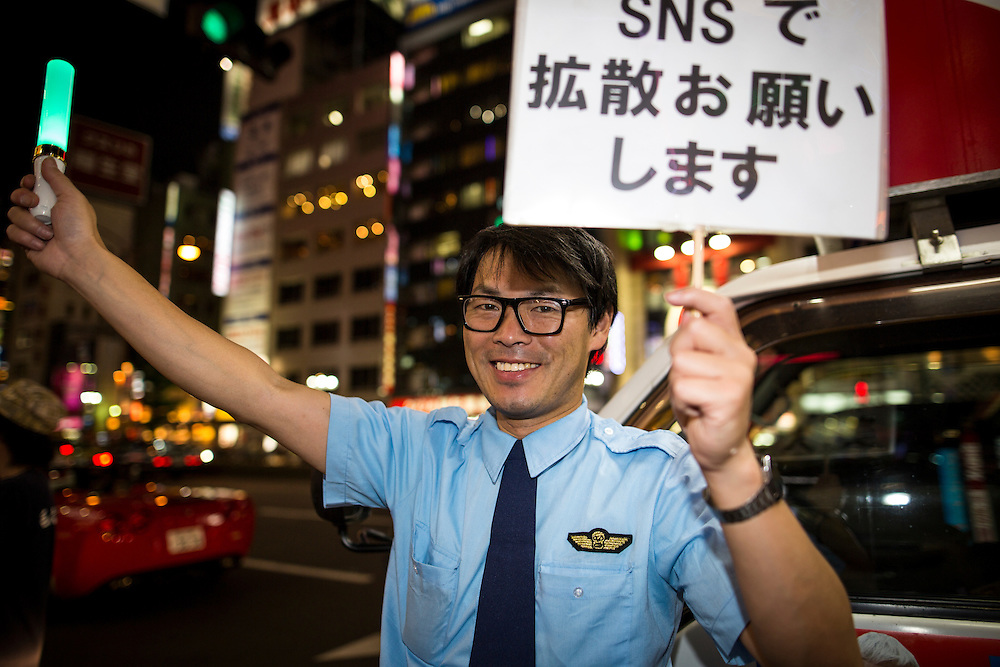 """TOKYO, JAPAN - JULY 20 : Supporter of Mac Akasaka with placards saying """"plese spread it by your SNS"""" during the campaign speech rally for the July 31 Tokyo gubernatorial election in Kabukicho, Tokyo, Japan on Wednesday, July 20, 2016.   (Photo: Richard Atrero de Guzman/NUR Photo)"""