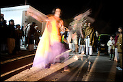 "Koumy, 26 years old, transvestite by the youth, membership of the middle class, during performance on the street at a wedding cerimony, where he  and his friend are the dancers for the bridegroom. Evening in countryside of Islamabad, Pakistan on Friday, November 28 2008.....""Not men nor women"". Just Hijira, Kusra. Painted lips, Kajal surrounding their eyes and colourful veils. Pakistan is today considered a strongly, foundamentalist as well, islamic country. But under its reputation, above all over the talebans' continuos advancing, stirs a completely extraneous world, a multiethnic mixed society. Transvestites make part of it, despite this would not be admitted by a strict law. Third gender, the Hijira are born as men (often ermaphrodites) or with an ambiguous genital situation, and they have their testicles and penis removed through a - often brutal - surgical operation. The peculiarity is that this operation does not contemplate the reconstruction of a female organ. This is the reason why they are not considered as men nor women, just Hijira. They are often discriminated, persecuted  and taxed with being men prostitutes in the muslim areas. The members of this chast perform dances during celebrations, especially during weddings, since it is anciently believed that an EUNUCO's dance and kiss in the wedding day brings good luck to the couple's fertility...To protect the identities of the recorded subjects names and specific places are fictionals."