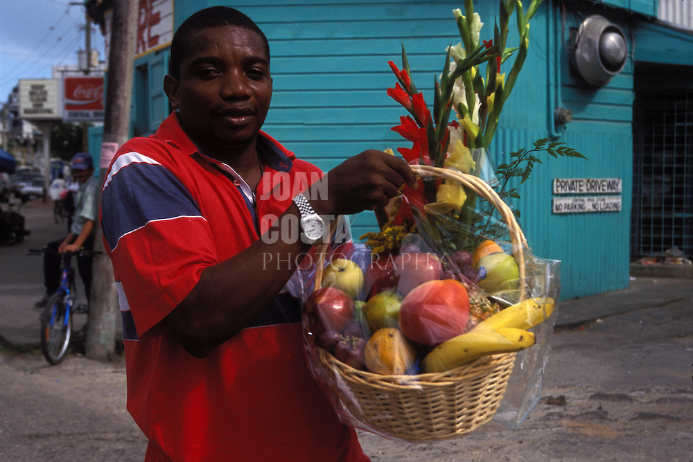 BELIZE/ Belize City / Young man carrying a fruit and flowers basket...© JOAN COSTA