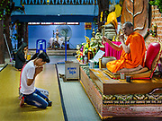 "30 DECEMBER 2017 - BANG KRUAI, NONTHABURI, THAILAND:  A monk blesses people in the basement of the prayer hall at Wat Ta Khien, about 45 minutes from Bangkok in Nonthaburi province. The temple is famous for the ""floating market"" on the canal that runs past the temple and for the ""resurrection ceremonies"" conducted by monks at the temple.      PHOTO BY JACK KURTZ"