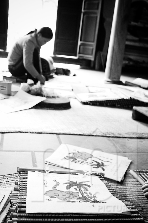 The diep paper is a Vietnamese-styled papyrus made from the do tree, together with seashells and after printing, the prints are treated and left out in the sun to dry. A woman is working on the background.