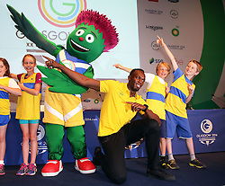 Image licensed to i-Images Picture Agency. 26/07/2014. Glasgow, United Kingdom. Usain Bolt  strikes his famous Lightning pose with local children and the Commonwealth Games mascot  on day three of the Games in Glasgow where he confirmed his attendance in the Relay event.  Picture by Stephen Lock / i-Images