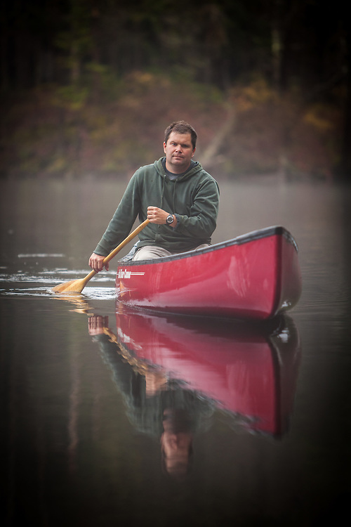 Rich Anderson paddling a canoe through fog on a quiet Adirondack pond, New York.