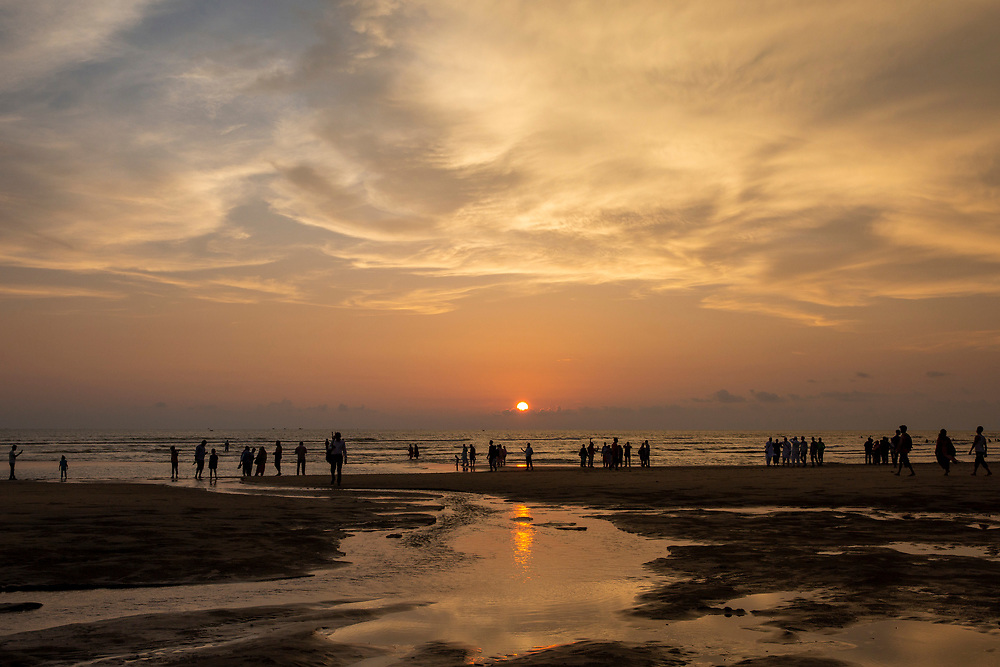 People walk in and along the shoreline of Laboni Beach, Cox Bazar, Chittagong Division, Bangladesh, Asia. The sun is setting behind clouds in the sky and the warm orange sunlight is reflected in the estuary water leading out to the sea. (photo by Andrew Aitchison / In pictures via Getty Images)