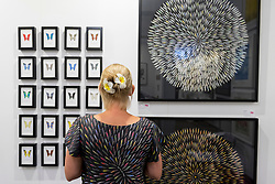 © Licensed to London News Pictures. 06/10/2016. London, UK. A woman stands in front of artworks made from a variety of scalpel and Stanley knife blades at the preview of Moniker Art Fair, part of London Art Week, taking place at the Old Truman Brewery, near Brick Lane.  Now in its seventh year, the fair embraces contemporary art from emerging and established artists, the majority of whom attend the fair in person in order to meet potential collectors and to show their work. Photo credit : Stephen Chung/LNP
