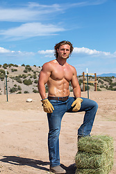 shirtless muscular man in jeans on a ranch