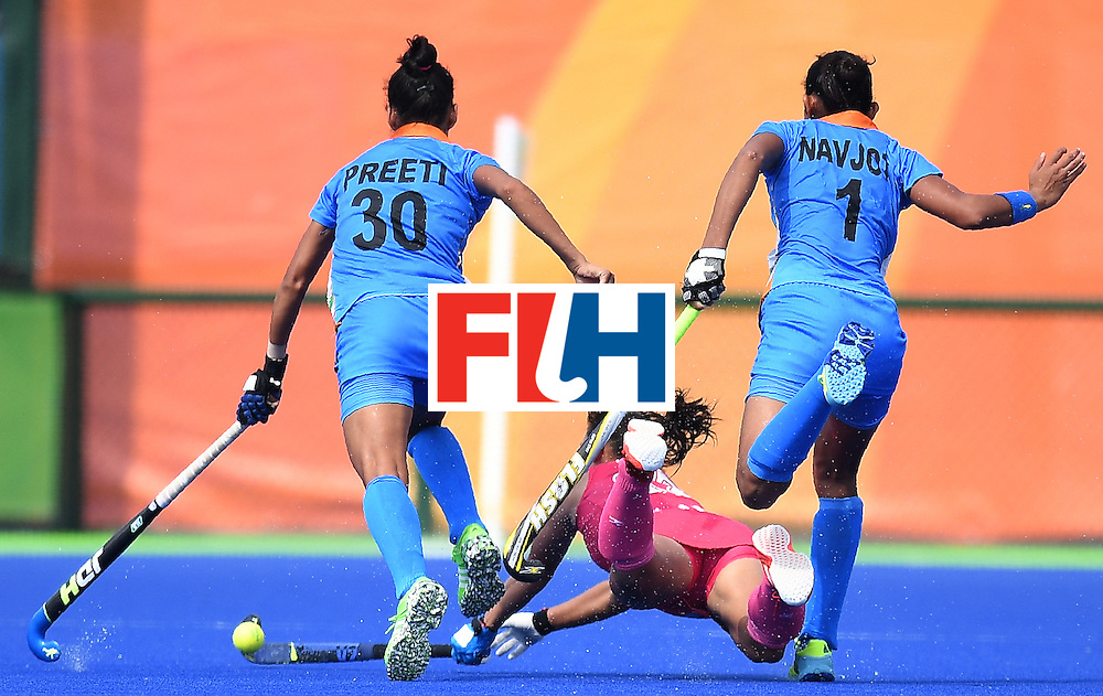 Japan's Yukari Mano (C) hits the ball as India's Preeti Dubey (L) and Navjot Kaur chase during the women's field hockey Japan vs India match of the Rio 2016 Olympics Games at the Olympic Hockey Centre in Rio de Janeiro on August, 7 2016. / AFP / MANAN VATSYAYANA        (Photo credit should read MANAN VATSYAYANA/AFP/Getty Images)