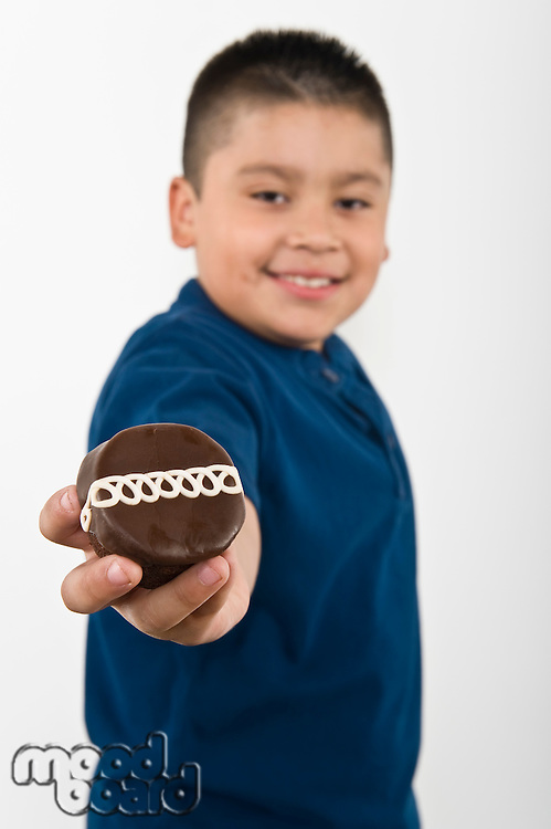 Pre-teen (10-12) boy holding out cookie