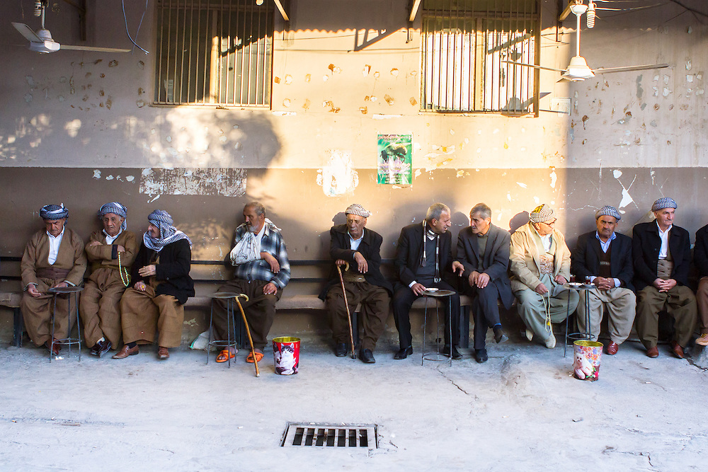 LICENSED BY GETTY IMAGES. Iraqi Kurdish men, wearing traditional baggy trousers and headscarves, passing time in the late afternoon sun, having tea and playing with their prayer chains, on the street outside a tea house in the old bazar of Dohuk (a.k.a. Duhok), Iraqi Kurdistan, Iraq.