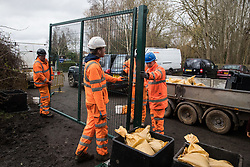 Harefield, UK. 13 January, 2020. A team of HS2 construction engineers erects a gate across a public right of way leading to a protection camp established by Stop HS2 activists. Part of the nearby Colne Valley protection camp was evicted by bailiffs last week. 108 ancient woodlands are set to be destroyed by the high-speed rail link and further destruction of trees for HS2 in the Harvil Road area is believed to be imminent.