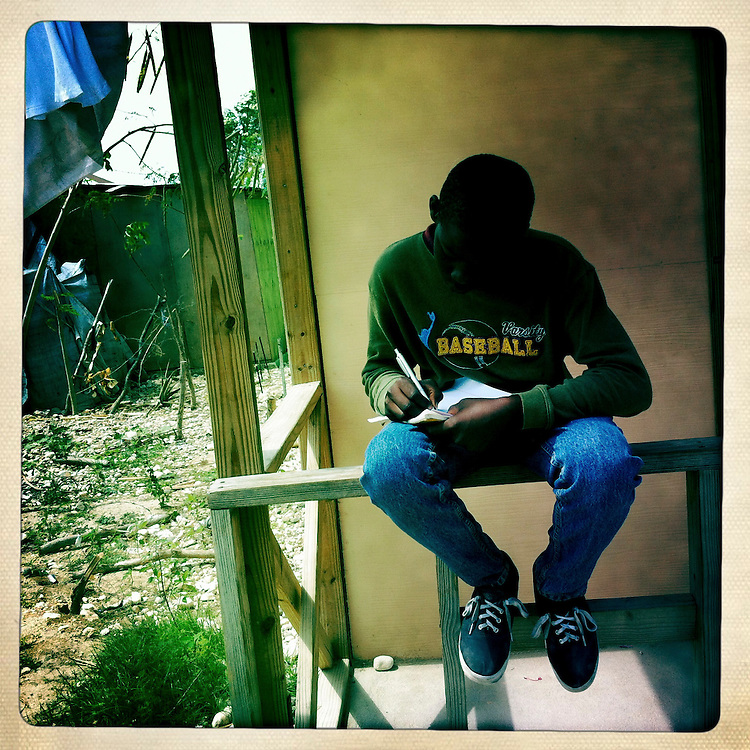 A boy writes a letter to his American penpal at the Corail camp on Thursday, April 5, 2012 in Port-au-Prince, Haiti.