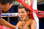 02 JULY 2006 - PHNOM PENH, CAMBODIA: A boxer gets advice from his corner man during a traditional Khmer boxing match in Phnom Penh, Cambodia. Khmer boxing is the same sport as Muay Thai (traditional Thai kick boxing) but because off animosity between Thailand and Cambodia it is called Khmer Boxing in Cambodia. The Cambodians claim to have invented the sport, which is also practiced in Laos and Burma. Photo by Jack Kurtz