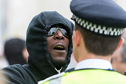 """© Licensed to London News Pictures. 09/07/2016. London, UK. A local resident confronts a policeman during a """"Black Lives Matter"""" rally in Brixton, to show solidarity with those who lost their lives in recent police related incidents in the USA. Photo credit : Stephen Chung/LNP"""