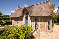 Thatched cottage made with a wall of standing granite stones