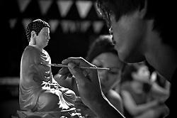 A vietnamese man paints carefully a miniature buddha statue. Nha Trang, Vietnam, Asia