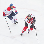 Josh Manson #3 of the Northeastern Huskies and Joe Pendenza #14 of the UMass Lowell Riverhawks in action during the Frozen Fenway game between The Northeastern Huskies and The UMass Lowell Riverhawks at Fenway Park on January 11, 2014 in Boston, Massachusetts.