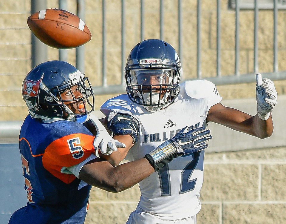 Costa Mesa, California --Orange Coast College Defendsive End Semaj Bilal covers Fullerton College Receiver Justin Walker on a incoming pass during Saturday's game at LeBard Stadium.
