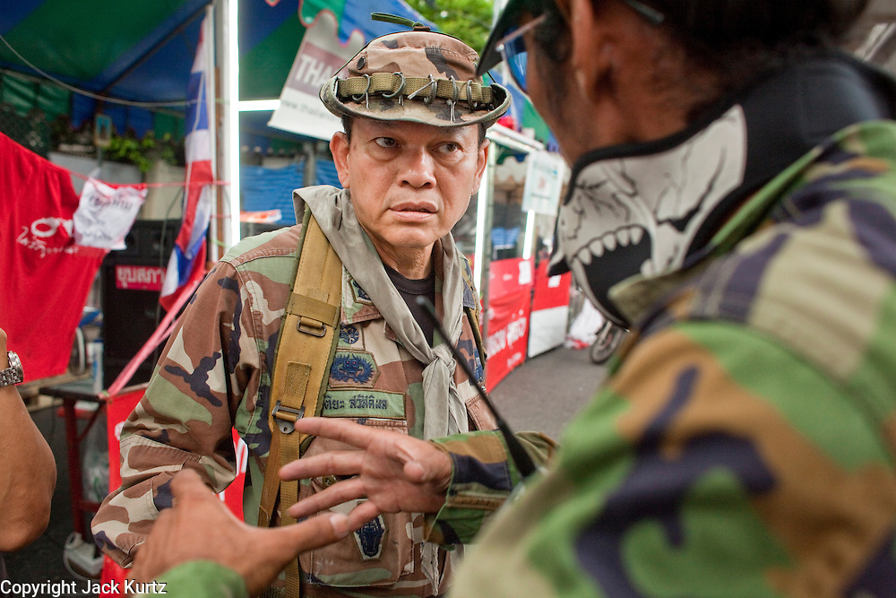 "May 12 - BANGKOK, THAILAND: Maj. Gen. KHATTIYA ""Seh Daeng"" SAWASDIPOL (LEFT) talks to a Red Shirt security official at a Red Shirt barricade in the Red Shirt camp in Bangkok Wednesday. Seh Daeng, as he is known, has emerged as the Red Shirts unofficial military commander. He has organized the barricades that ring the Red Shirt camp and has threatened to organize a guerilla campaign against the government if the Red Shirt protest is crushed by force. Seh Daeng is a hero to many Thais because he is credited with crushing Thailand's communist insurgency in the 1970's and 80's. He was the commander of Thailand's Internal Security Operations Command but after his political activities became apparent he was made the head aerobics instructor for the Thai army. He is now seen as one of the major personalities destabilizing the country and the government alleges that he is behind many of the grenade attacks and drive by shootings directed at government buildings and officials and he is wanted for a long list of felony offenses including weapons charges and terrorism related charges. Although some Red Shirts have officially repudiated him, he is still frequently seen around the Reds' barricades. The army has started proceedings to fire him, but he remains a general on active duty.   Photo by Jack Kurtz"