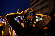 Protester William Estrella ties a black bandana around his face as he and others march through the streets of Tampa, Fla. during the 2012 Republican National Convention on August 29, 2012. The demonstrators took sandwiches to the homeless, picked up trash off of the street and spoke out against police brutality.