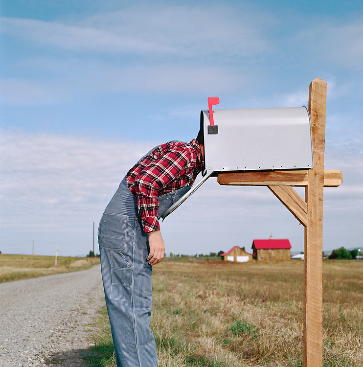 Man dressed in farmer clothes sticking head in mailbox on a country road.
