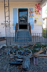 25 Oct, 2005. New Orleans, Louisiana.  Hurricane Katrina aftermath.<br /> The 8th ward lies in ruins following Katrina's devastating floods. A wheelchair lies in the dried mud outside a home where '1 dead in attic' is crossed out in graffiti on the front of the house.<br /> Photo; &copy;Charlie Varley/varleypix.com