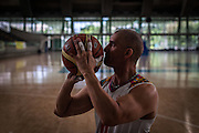 "2016/04/19 – Medellín, Colombia: Oscar Rios, 42, prepares to throws the ball to the basket during the training warm-up session of Antioquia's team at Atanasio Girardot Stadium, Medellin, 19th March, 2016.  <br /> -<br /> After his military service Oscar started to work as a bodyguard for a public prosecutor, a time of great violence in Medellin, during the 1990's when Pablo Escobar ran the city. <br /> On an assassination attempt of the public prosecutor, Oscar was shot seven times by Escobar's assassins. As a result he lost the mobility of his legs and feet, becoming paraplegic. <br /> The adaptation to a new life was hard, but he decided that he had to separate the injury under his waist from his head, and to keep doing what he wanted. Oscar had always liked basketball, so he decided to dedicate himself to it. In 1998 he became part of Team Colombia on wheelchair basketball. During his successful career he was several time South American Champion, was with Colombia on the top ten teams at the 2014 World Championship in Korea and went to the 2012 Paralympic Games in London. Unfortunately, this year Colombia missed the qualification for the Rio 2016 Paralympic, which was Oscar last opportunity to be back at an Olympics. <br /> He plans to retire soon and became a full-time basketball coach. Oscar believes that there is much talent in Colombia that needs to be fostered. When asked about the accident and his life on the wheelchair, Oscar says, ""Before I was an arrogant person and didn't have any love to give to my family. The accident was a blessing that made me a better, happier man and to appreciate more my life and family. If I was going to be born tomorrow, I wanted to be born on a wheelchair"". (Eduardo Leal)"