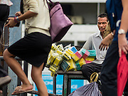 20 JULY 2015 - BANGKOK, THAILAND:   People getting off of a commuter boat walk past a sponge vendor waiting to board a Chao Phraya Express Boat to take his sponges in to Bangkok. He is waiting a pier that is just south of the Chao Phraya River promenade project. The Chao Phraya promenade is development project of parks, walkways and recreational areas on the Chao Phraya River between Pin Klao and Phra Nang Klao Bridges. The 14 kilometer long promenade will cost approximately 14 billion Baht (407 million US Dollars). The project involves the forced eviction of more than 200 communities of people who live along the river, a dozen riverfront  temples, several schools, and privately-owned piers on both sides of the Chao Phraya River. Construction is scheduled on the project is scheduled to start in early 2016. There has been very little public input on the planned redevelopment.         PHOTO BY JACK KURTZ