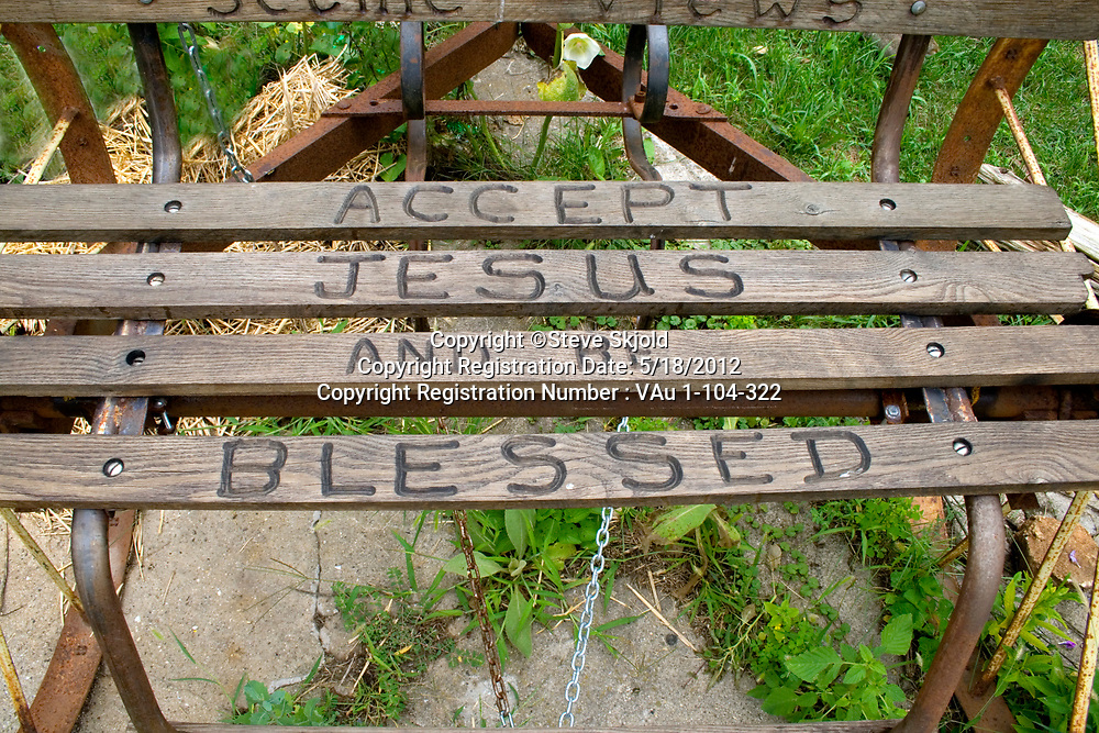 Norma's flower garden with antique bench carved with the reminder to Accept Jesus and be blessed. Lanesboro Minnesota MN USA