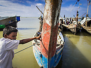 07 NOVEMBER 2014 - SITTWE, RAKHINE, MYANMAR:  A Rohingya boy leans against the prow of a boat in the port of a Rohingya IDP camp near Sittwe. The government of Myanmar has forced more than 140,000 Rohingya Muslims who used to live in Sittwe, Myanmar, into squalid Internal Displaced Person (IDP) camps. The forced relocation took place in 2012 after sectarian violence devastated Rohingya communities in Sittwe and left hundreds dead. None of the camps have electricity and some have been denied access to regular rations for nine months. Conditions for the Rohingya in the camps have fueled an exodus of Rohingya refugees to Malaysia and Thailand. Tens of thousands have put to sea in rickety boats hoping to land in Malaysia but sometimes landing in Thailand. The exodus has fueled the boat building boom on the waterfront near the camps. Authorities expect the pace of refugees fleeing Myanmar to accelerate during the cool season, December through February, when there are fewer storms in the Andaman Sea and Bay of Bengal.  PHOTO BY JACK KURTZ