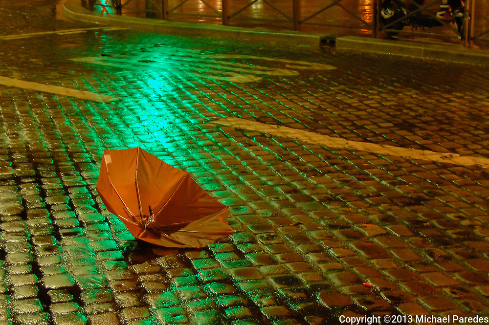 A lonely umbrella ends up on a rain-slicked Paris street