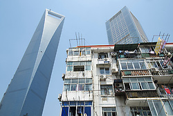Contrast between d apartment buiding with modern skyscrapers to rear in Lujiazui financial district in Shanghai China