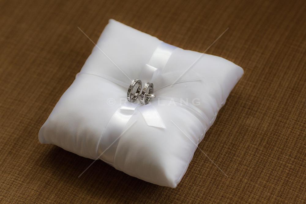 silver wedding rings on a satan pillow