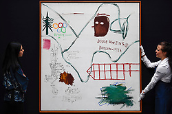 "© Licensed to London News Pictures. 21/06/2019. LONDON, UK. A staff member and a technician with ""Big Snow"", 1984, by Jean-Michel Basquiat (Est. GBP 3.5-4.5m) at the preview of a Contemporary Art auction at Sotheby's New Bond Street.  The sales take place 26 and 27 June 2019.  Photo credit: Stephen Chung/LNP"