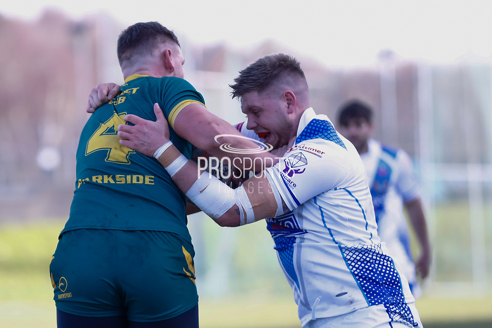 Hunslet Club Parkside centre Michael Waite (4) is tackles by Workington Town loose forward Joseph Ryan (13)  during the Ladbrokes Challenge Cup round 3 match between Hunslet Club Parkside and Workington Town at South Leeds Stadium, Leeds, United Kingdom on 24 February 2018. Picture by Simon Davies.