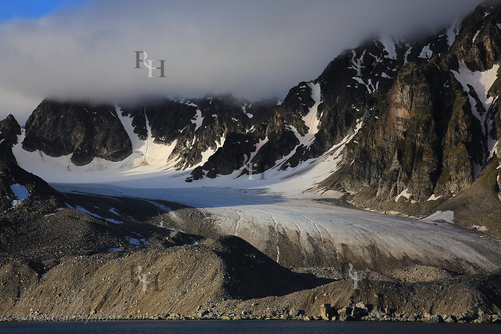 Glacier that once reached the sea stops short amid rocky moraines in Smeerenburgfjorden on the north coast of Spitsbergen island; Svalbard, Norway.