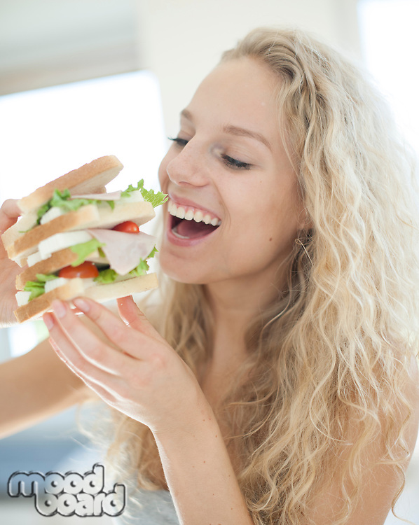 Happy woman eating large sandwich in house