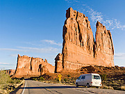 "The orange sandstone Courthouse Towers resist erosion in Arches National Park, Utah, USA. These rock monuments are beautiful both at sunrise (seen here) and sunset. A Volkswagon Eurovan Camper parks at a pullout. Published in ""Light Travel: Photography on the Go"" by Tom Dempsey 2009, 2010."
