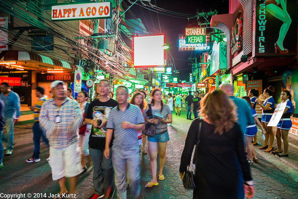 """26 SEPTEMBER 2014 - PATTAYA, CHONBURI, THAILAND: Tourists on Walking Street, the red light district in Pataya. Pataya, a beach resort about two hours from Bangkok, has wrestled with a reputation of having a high crime rate and being a haven for sex tourism. After the coup in May, the military government cracked down on other Thai beach resorts, notably Phuket and Hua Hin, putting military officers in charge of law enforcement and cleaning up unlicensed businesses that encroached on beaches. Pattaya city officials have launched their own crackdown and clean up in order to prevent a military crackdown. City officials have vowed to remake Pattaya as a """"family friendly"""" destination. City police and tourist police now patrol """"Walking Street,"""" Pattaya's notorious red light district, and officials are cracking down on unlicensed businesses on the beach.     PHOTO BY JACK KURTZ"""