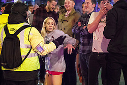 "© Licensed to London News Pictures . 16/12/2017. Manchester, UK. A man , believed to have been injured in a fight with another man , stems blood flowing from his nose as a friend wearing a blood-stained sweat shirt, hails a taxicab . Revellers out in Manchester City Centre overnight during "" Mad Friday "" , named for historically being one of the busiest nights of the year for the emergency services in the UK . Photo credit: Joel Goodman/LNP"