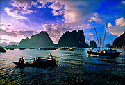 On the emerald waters of Vietnam's Gulf of Tonkin, sampans glide through Halong Bay, where limestone cliffs and rocky outcroppings of tropical hardwoods rise from the sea. A UNESCO World Heritage site with some 1,600-plus islands, Halong Bay today is overwhelmed with tourists arriving in buses, sail boats, cruise ships, and hundreds of the country's famous longboats.  © Steve Raymer / National Geographic Creative