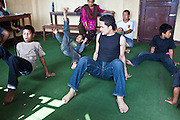 A Nepalese teacher demonstrates a dance move to young street-children in the Voice of Children rehabilitation center in Kathmandu, Nepal. The not-for-profit organisation supports street children and those who are at risk of sexual abuse through educational and vocational training opportunities, health services and psychosocial counseling.