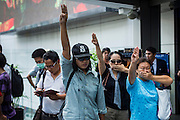 "01 JUNE 2014 - BANGKOK, THAILAND: Thais hold up a three fingered salute during a protest against the Thai military coup at Terminal 21 a popular shopping mall in Bangkok. The salute is from the movie ""The Hunger Games"" and symbolizes it admiration, thanks and good-bye to a loved one. In this case, the loved one is reportedly Thai democracy. The Thai army seized power in a coup that unseated a democratically elected government on May 22. Since then there have been sporadic protests against the coup. The protests Sunday were the largest in several days and seemed to be spontaneous ""flash mobs"" that appeared at shopping centers in Bangkok and then broke up when soldiers arrived. Protest against the coup is illegal and the junta has threatened to arrest anyone who protests the coup. There was a massive security operation in Bangkok Sunday that shut down several shopping areas to prevent the protests but protestors went to malls that had no military presence.    PHOTO BY JACK KURTZ"