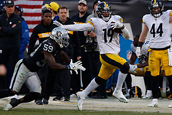 OAKLAND, CA - DECEMBER 09: Wide receiver JuJu Smith-Schuster #19 of the Pittsburgh Steelers breaks a tackle from linebacker Tahir Whitehead #59 of the Oakland Raiders during the fourth quarter at the Oakland Coliseum on December 9, 2018 in Oakland, California. The Oakland Raiders defeated the Pittsburgh Steelers 24-21. (Photo by Jason O. Watson/Getty Images) *** Local Caption *** JuJu Smith-Schuster; Tahir Whitehead