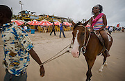 A woman rides a horse at Labadi Beach in Accra, Ghana on Sunday October 8, 2007. Also known as La Pleasure Beach, it is one of the city's most popular hangouts, especially on Sunday afternoons. For a small fee, visitors can ride horse along the ocean.