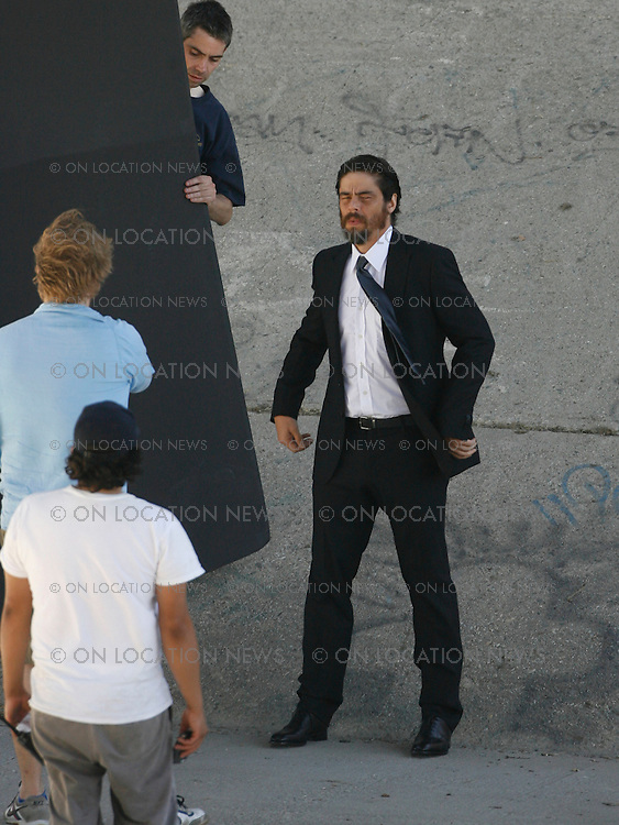 LOS ANGELES , CALIFORNIA, Monday, July 2nd 2007. EXCLUSIVE: Actor Benicio Del Toro poses for a photo shoot for men's 'Esquire' magazine in the LA river bed. Del Toro who is presently shooting a bio pic about Argentine revolutionary hero 'Che Geuevara' was dressed in a black suit & tie in the 90 degree downtown heat. Benicio seemed to be having fun at the shoot especially when he spontaneously threw an 'Esquire' sign into the river. Photograph: Eric Ford/On Location News 1-818-613-3955 info@onlocationnews.com
