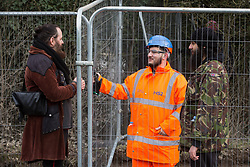 Harefield, UK. 8 February, 2020. Environmental activists chat to a HS2 engineer behind Heras-style fencing on Harvil Road in the Colne Valley erected in preparation for tree felling work for the high-speed rail link. Environmental activists based at a series of wildlife protection camps in the area used a variety of tactics to prevent the tree felling work, for which road and rail closures had been implemented, for the duration of the weekend for which it had been scheduled.