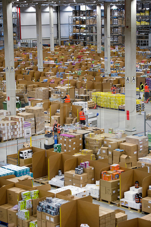 © London News Pictures. File pic dated. 13/12/2012. Swansea, UK. Amazon have today (18/12/2012) announced that they will begin this years sales at 9am on Christmas morning. Staff at the Amazon Swansea fulfilment centre process orders as they prepare their busiest time of the year. The 800,000 sq ft fulfilment centre, the largest of Amazon's plants in England and Whales, is big enough to hold 10 football pitches. Over 1,000 extra jobs are created at the centre to cope with the extra seasonal workload. Photo credit: LNP