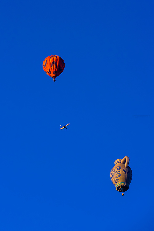 Hot air balloons in the sky with a commerical jet aircraft in background, Albuquerque International Balloon Fiesta, Albuquerque, New Mexico USA.