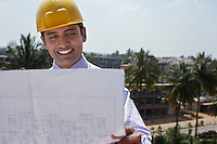 Architect wearing a yellow hard hat looking at blue prints at construction site