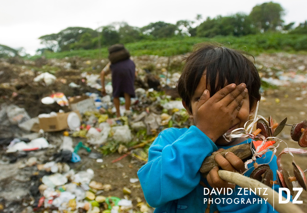 A boy plays peek-a-boo amongst piles of garbage as his mother searches through the community dump for food and valuables in Jinotepe, Nicaragua on October 3, 2004. Nicaragua is the second poorest country in the western hemisphere.